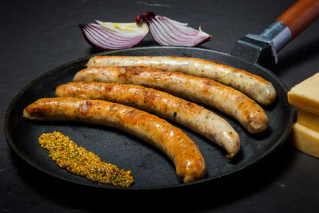 Big frying pan with fried thin meat sausages and granular mustard served with hard cheese and sliced onion on black background