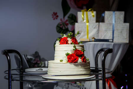 Two-tiered white wedding cake decorated with red and pink roses served on glass tray against gift boxes Фото со стока
