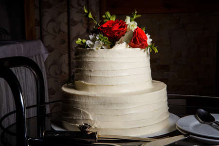 Appetizing two-tiered delicious creamy wedding cake decorated with red and white roses on dark background