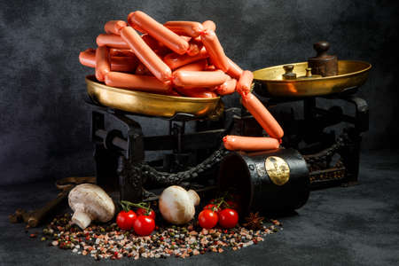 big pile of uncooked long thin wieners on antiquarian scales with mushrooms and tomatoes cherry on black background