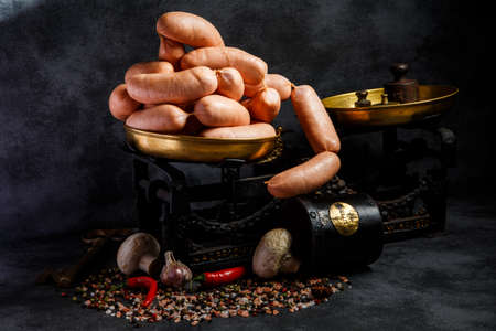 raw short thick wieners rolled in spiral on antiquarian scales with garlic, red chili pepper and white mushrooms Stock Photo