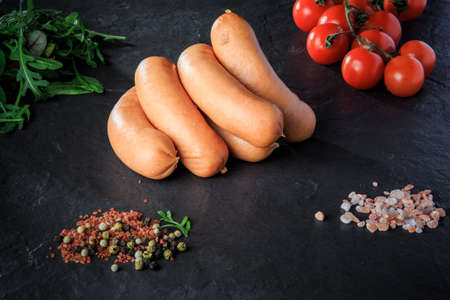small set of raw short thick sausages with pink salt, spices, green rucola and tomatoes cherry on black background Stockfoto