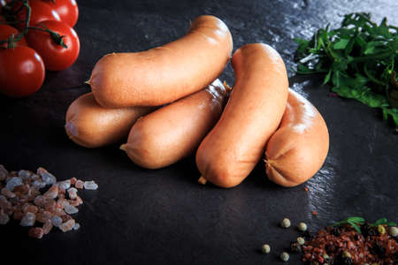macro set of thick short sausages with pink salt, spices, green rucola and tomatoes cherry on black background Stockfoto