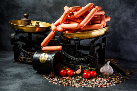 large pile of raw long thin wieners on antiquarian scales with whole garlic and tomatoes cherry on black background