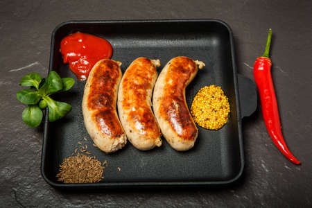 top view square pan with fried sausages, ketchup, caraway and granular mustard served with chili pepper and green basil