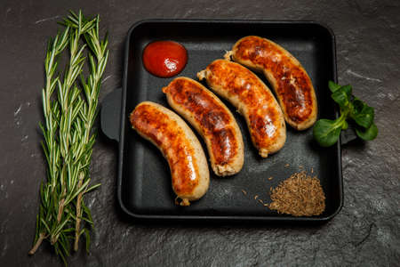 top view square pan with four fried sausages, ketchup, caraway seeds served with green rosemary and basil on black background Фото со стока
