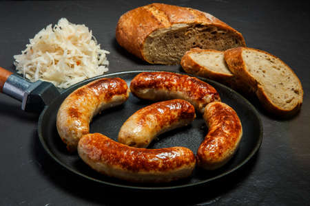 five tasty ruddy meat wieners fried in large pan served with sliced rye bread and sauerkraut on black background Stock Photo