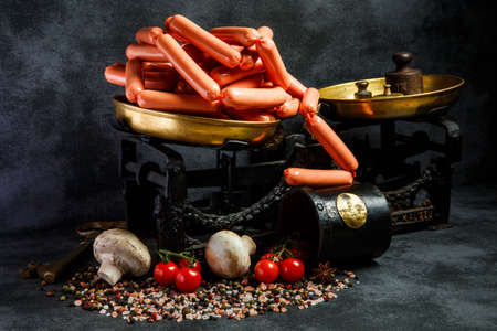big heap of uncooked long thin wieners on antiquarian scales with mushrooms and tomatoes cherry on black background