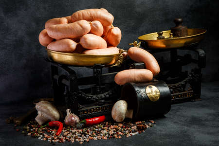 bunch of short thick wieners rolled in spiral on antiquarian scales with red chili pepper and white mushrooms