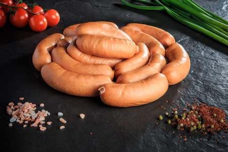 circle set of uncooked short sausages served with salt, spices, green onion and tomatoes cherry on black background Stockfoto