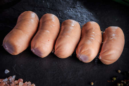 closeup row of raw short thick sausages with pink salt and aromatic spices on black background