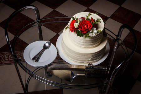 top view on two-tiered white creamy wedding cake with red and pink roses served on glass tray with plates and spoons