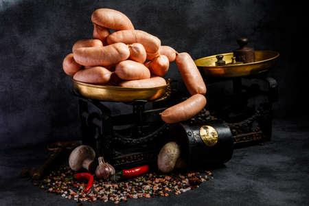 bunch of raw short thick wieners rolled in spiral on antiquarian scales with chili pepper and white mushrooms