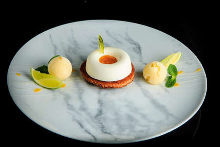 top view on white mini mousse cake served with two spheres of ice cream and sliced limes served on black background