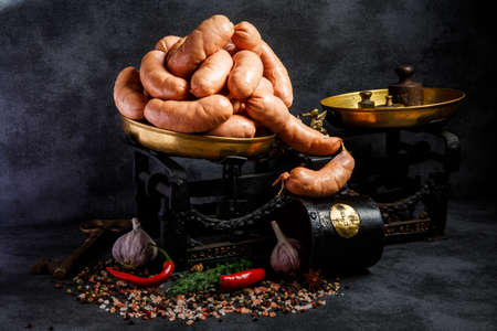 group of raw short thick wieners rolled in spiral on antiquarian scales with green dill, chili pepper, whole garlic