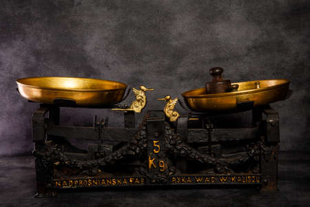 old vintage antiquarian weighing scales with two golden bowls and small black weight on black background