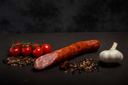 delicatessenlong chunk of smoked dry sausage with garlic and tomatoes