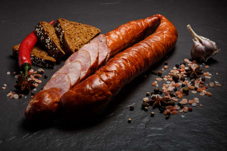 closeup sliced dry smoked sausage with garlic, chili and rye bread
