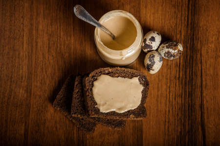 Top view on jar of homemade tahini sesame seeds butter with spoon served with quail eggs and rye bread slices