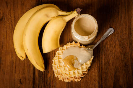top view on tahini butter jar, bananas, spoon on belgian waffles with tahini and honey on wooden background Stok Fotoğraf