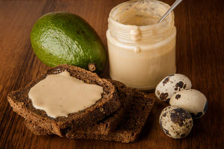 top view closeup tahini butter in glass jar, sliced rye bread, whole avocado, and three quail eggs on wooden background