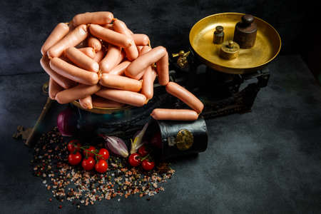 top view of large pile of raw long thin wieners on antiquarian scales served with sliced onion and tomatoes cherry