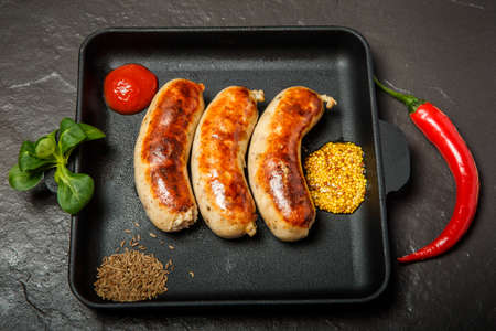 top view square pan with three fried sausages, ketchup, caraway and granular mustard served with chili pepper and green basil