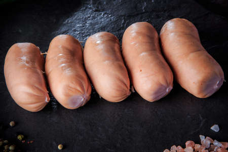 closeup small row of five short thick sausages with pink salt and aromatic spices on black background Stock fotó