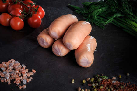 group of five raw thick short sausages with pink salt, spices, green onion, dill and tomatoes cherry on black background