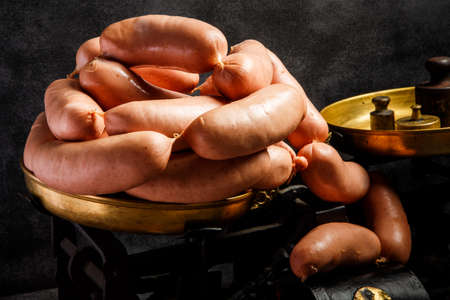 big bunch of raw short thick wieners with natural casings rolled in spiral on antiquarian scales over black background