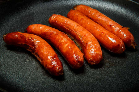closeup five short fried hunting sausages served on round black pan on black background Stock fotó