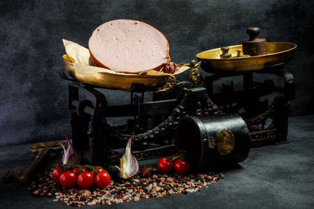 big piece of appetizing boiled sausage on craft paper on antique scales served with sliced onion and tomatoes cherry
