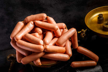 closeup big heap of raw long thin wieners with natural casings served on antiquarian scales over black background Stock fotó