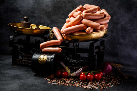 big heap of short thick wieners rolled in spiral on antiquarian scales with spices, onion slices and tomatoes cherry