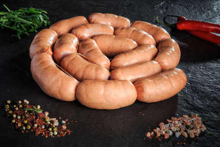 circle set of uncooked short thick sausages served with pink salt, spices, rucola and red chili pepper on black background