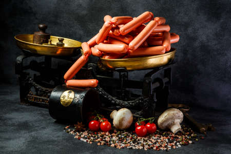 big heap of raw long thin wieners on antiquarian scales with mushrooms and tomatoes cherry on black background Stock Photo