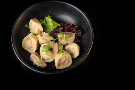 top view on steamed meat dumplings stuffed with meat served with salad leaves in deep bowl on black background