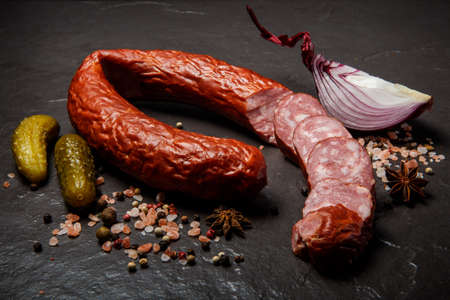 closeup spicy dry cured sausage with served with pink salt, spices, two pickled cucumbers and slice of onion Stock fotó