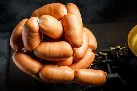 closeup set of short thick wieners rolled in spiral on scales Stock Photo