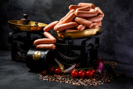 large group of uncooked thin wieners on antiquarian scales served with sliced onion and tomatoes cherry