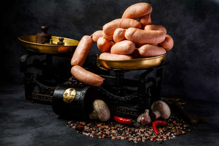 bunch of short thick wieners rolled in spiral on antiquarian scales with garlic, red chili pepper and white mushrooms
