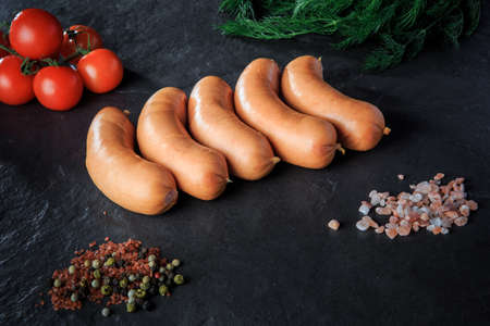row of five raw short thick sausages with dill and tomatoes
