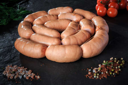 circle set of raw short sausages with rucola and tomatoes