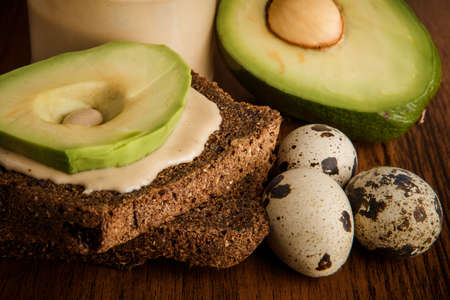 macro of three quail eggs, sliced avocado on rye bread slices, and tahini butter in glass jar on wooden background