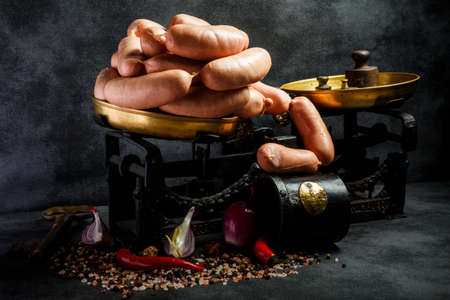 large pile of tasty thick wieners rolled in spiral on antiquarian scales with spices, onion slices and chili pepper