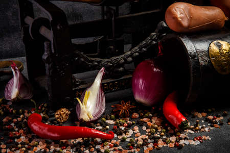 Closeup heap of spices, pink salt, chili pepper, sliced onion and raw wieners on antiquarian scales on black background