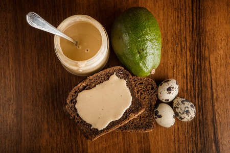 top view on tahini butter in glass jar, sliced rye bread, whole green avocado, and three quail eggs on wooden background