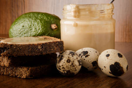 macro on three quail eggs, tahini butter in glass jar, rye bread slices, and whole green avocado on wooden background Stok Fotoğraf
