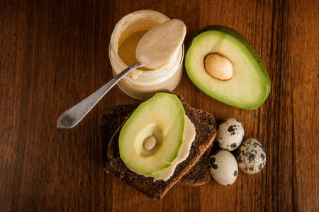 top view of three quail eggs, sliced avocado on rye bread, and tahini in glass jar with spoon on wooden background