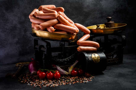 delicatessen long thin wieners on antiquarian scales served with sliced onion and tomatoes cherry